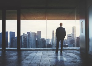 Young business man standing on a balcony and looking at city